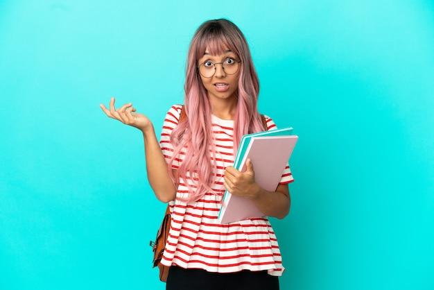 Молодая студентка с розовыми волосами изолирована на синем фоне с шокированным выражением лица