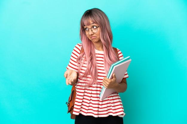 파란색 배경에 격리된 분홍색 머리를 가진 젊은 학생 여성이 옆을 바라보면서 놀란 표정을 하고 있습니다.
