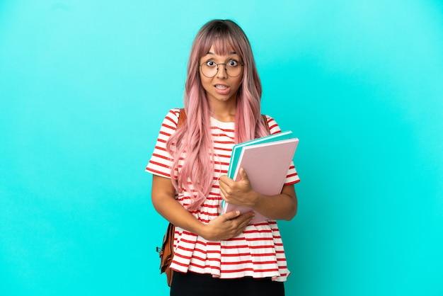 Молодая студентка с розовыми волосами изолирована на синем фоне с удивленным выражением лица