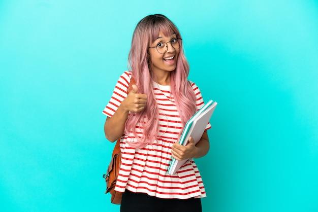 좋은 일이 생겨서 엄지손가락을 치켜들고 파란 배경에 고립된 분홍색 머리를 한 젊은 학생 여성