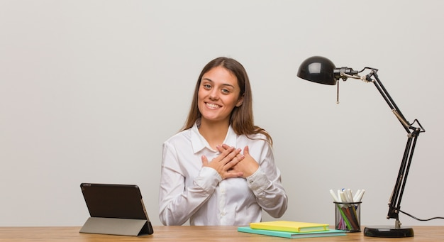 Young student woman working on her desk doing a romantic gesture