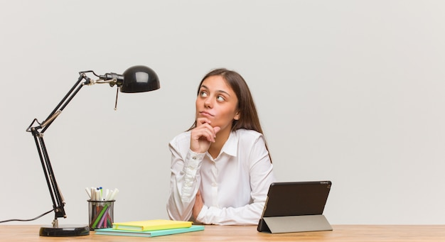 Young student woman working on her desk doubting and confused