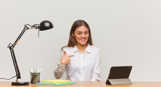 Young student woman working on her desk person pointing by hand to a shirt copy space, proud and confident