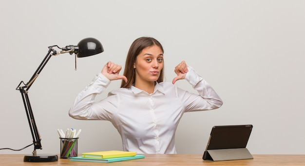 Young student woman working on her desk pointing fingers, example to follow