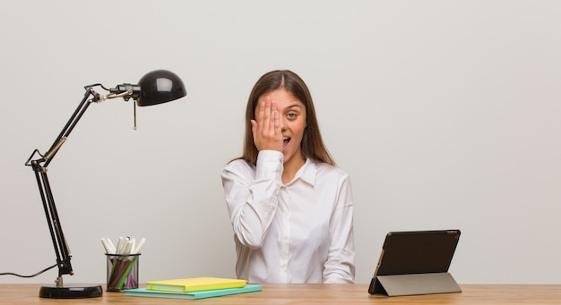 Young student woman working on her desk shouting happy and covering face with hand