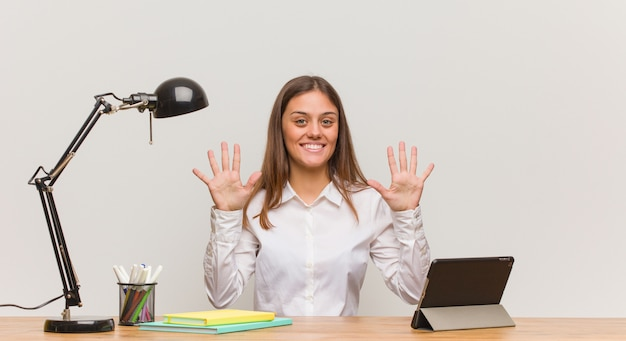 Young student woman working on her desk showing number ten