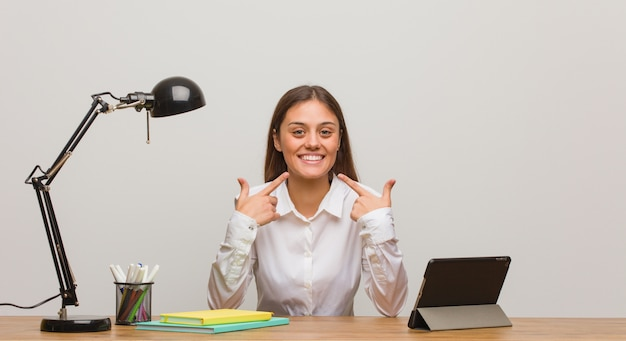 Young student woman working on her desk smiles, pointing mouth