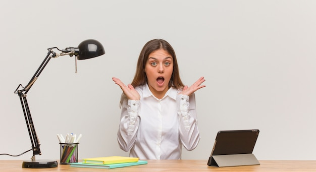 Young student woman working on her desk surprised and shocked