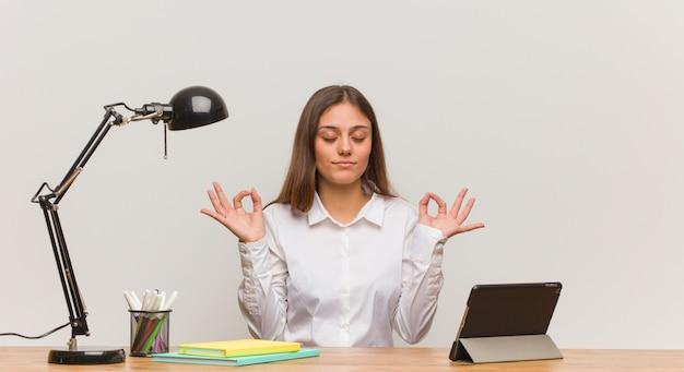 ヨガを行う彼女の机で働く若い学生女性