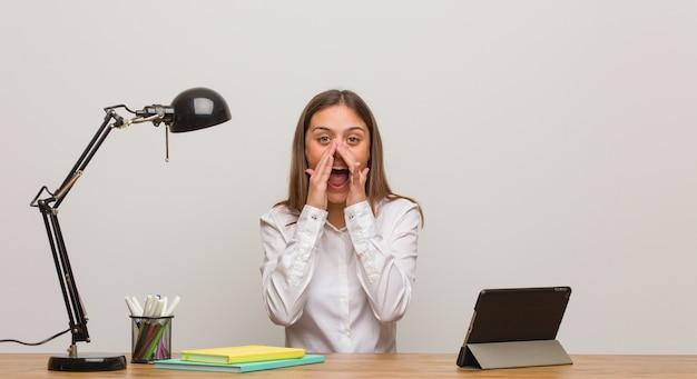 Молодая студентка женщина, работающая на своем столе, кричит что-то счастливое впереди
