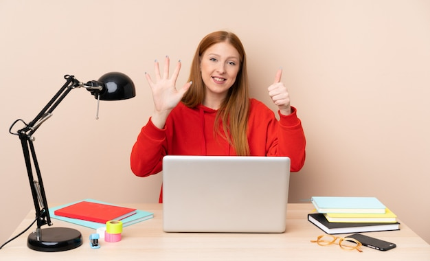 Young student woman in a workplace with a laptop counting six with fingers