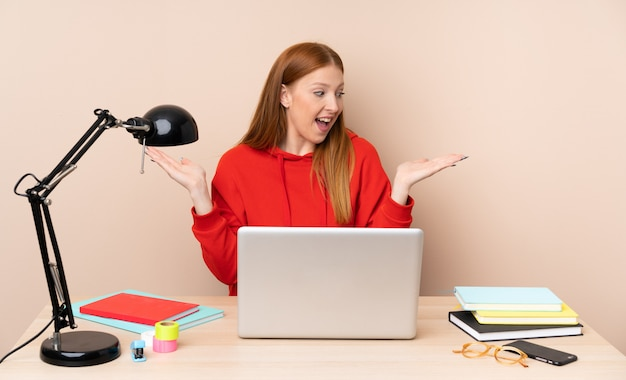 Young student woman in a workplace with a laptop holding copyspace with two hands