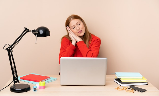 Young student woman in a workplace with a laptop making sleep gesture in dorable expression