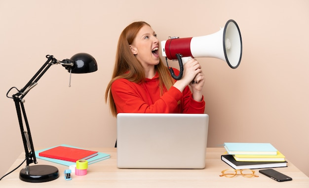 Young student woman in a workplace with a laptop shouting through a megaphone