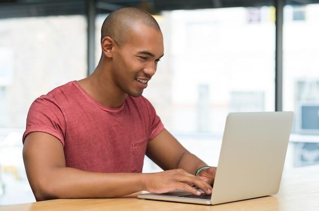 インターネットカフェでラップトップに取り組んでいる若い学生