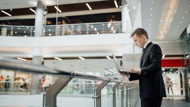 ノートブックに取り組んでいる若い学生、モール、屋内、縦断ビュー、ビジネスセンターで黒いスーツを着て