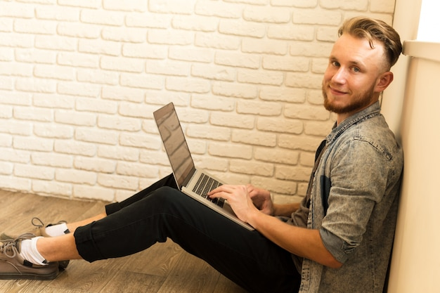 Young student works on his laptop at home