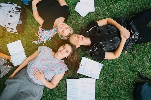 Молодые студенты, лежащие на траве