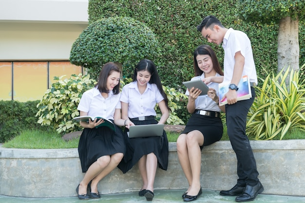 Young students play computer and reading book in university, lifestyle learning