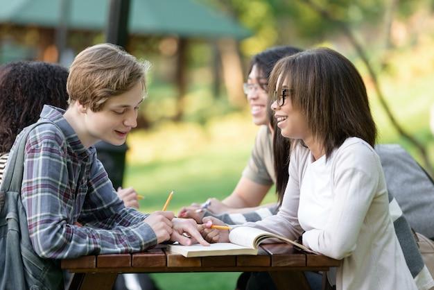 Молодые студенты сидят и учатся на открытом воздухе во время разговора