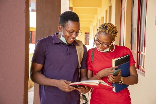 Молодые студенты в масках, держат книги и телефоны в кампусе