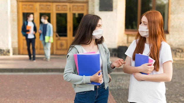 Young students with face masks discussing