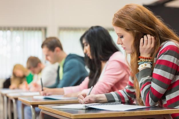 Молодые студенты, записывающие заметки в классе