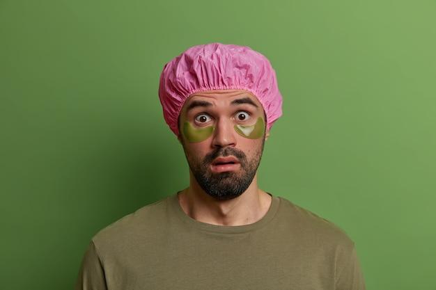 Молодой ошеломленный небритый европейский мужчина недоверчиво смотрит, узнает шокирующие новости, носит шапочку для ванны и зеленые пятна под глазами для уменьшения морщин и отечности, изолированный на зеленой стене