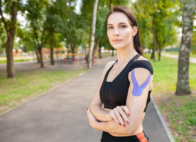 黒のスポーツ服を着ている若い見事な筋肉の女性