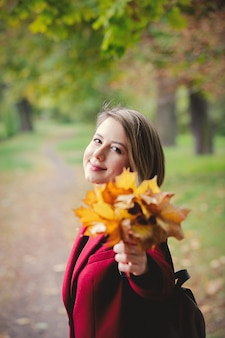 Young style girl with leaves in park alley