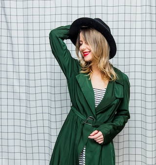 Young style woman in hat and green cloak in 90s style