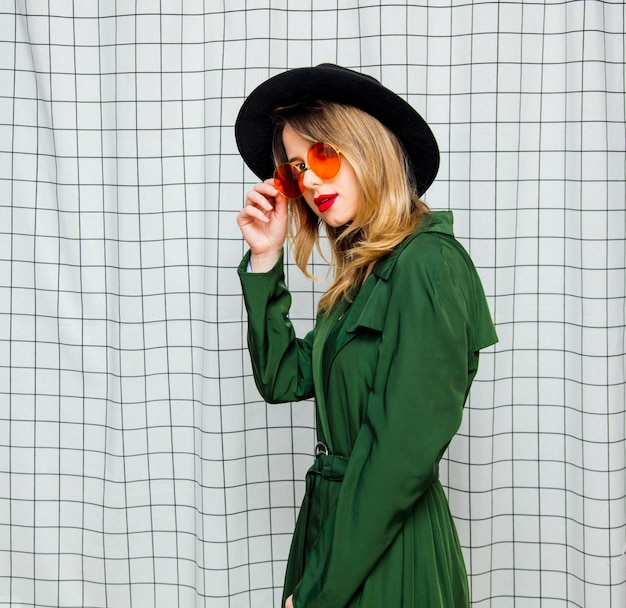 Young style woman in sunglasses and green cloak in 90s style