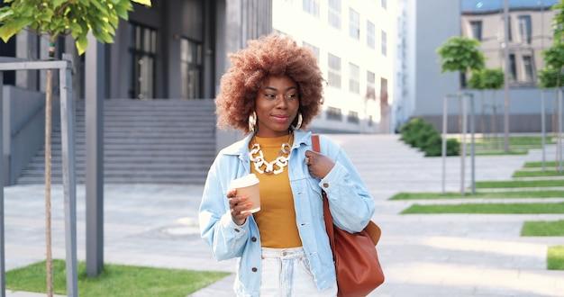街の通りを歩いて、持ち帰り用のコーヒーを飲み、嬉しそうに笑っているバッグを持つ若いスタイリッシュなアフリカ系アメリカ人の美しい巻き毛の女性。屋外を散歩し、温かい飲み物をすすりながら、かなり幸せな女性。