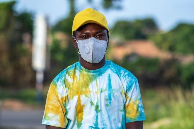 Giovane maschio afroamericano elegante in piedi all'aperto con una maschera protettiva
