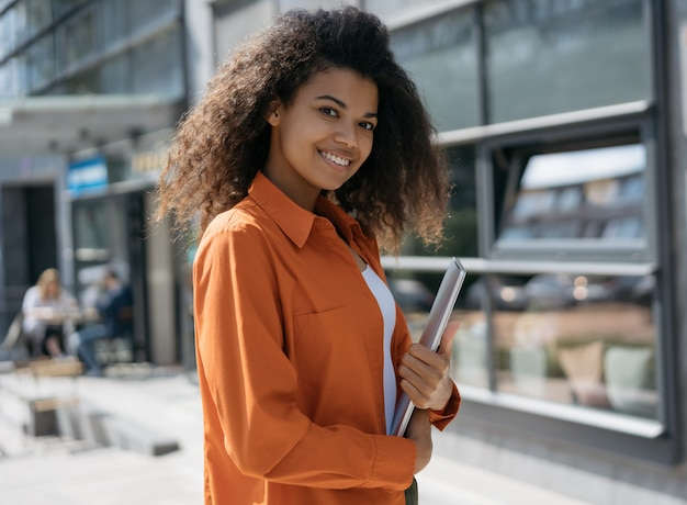 Young stylish african american woman holding laptop, walking on the street