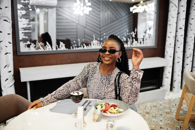 세련 된 젊은 아프리카 계 미국인 여자, 검은 색 선글라스를 착용하고 레스토랑에 앉아 와인과 함께 건강식을 즐기십시오.