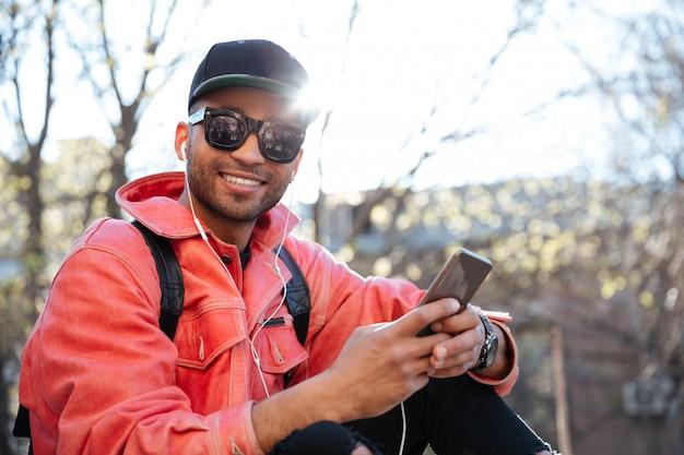 Молодой стильный афроамериканец в кепке и кожаной куртке