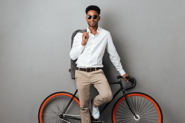 Молодой стильный афро-американский мужчина, стоя и опираясь на велосипеде