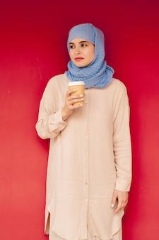 ヒジャーブとカジュアルな服装で赤い壁のそばに立っている間温かい飲み物を持っている若いスタイリッシュなアラビア女性