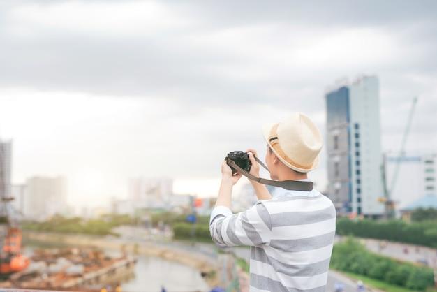 여행 가방과 카메라를 들고 여행하는 젊은 세련된 아시아 남자.