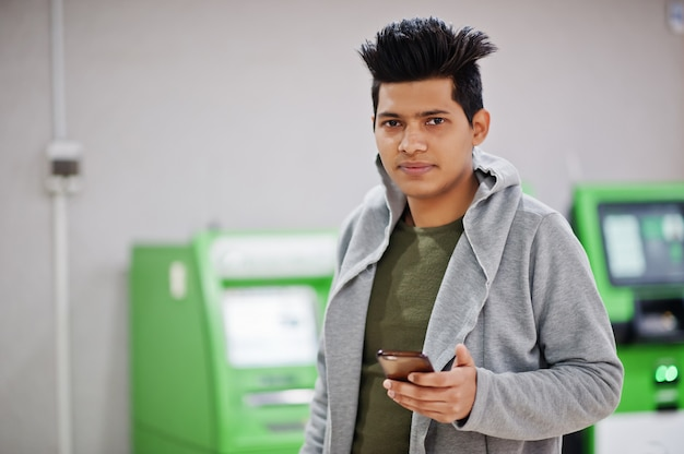 Young stylish asian man with mobile phone against row of green atm