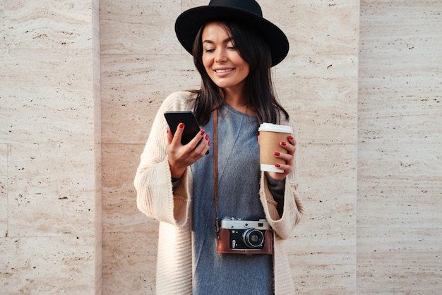 Young stylish asian woman in black hat using mobile phone and holding coffee cup while standing on street