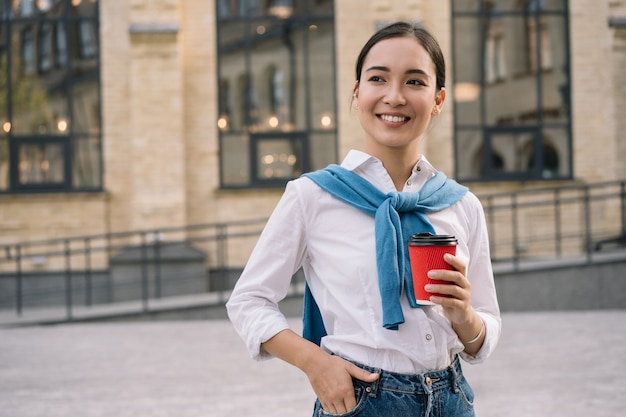 Young stylish asian woman holding cup of coffee, standing on urban street, waiting for taxi