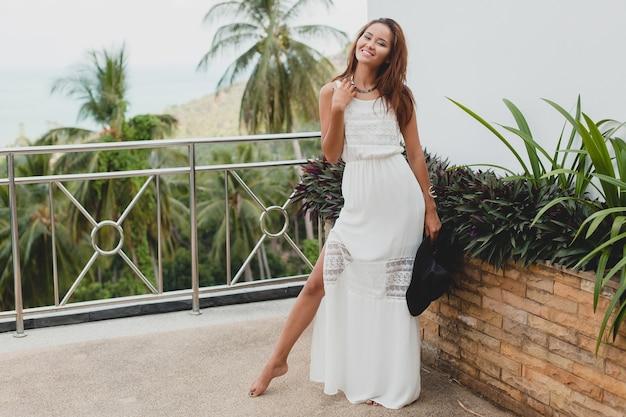 Молодая стильная азиатская женщина в белом платье бохо, винтажном стиле, естественном, улыбающемся, счастливом, тропическом отдыхе, отеле, фоне пальм
