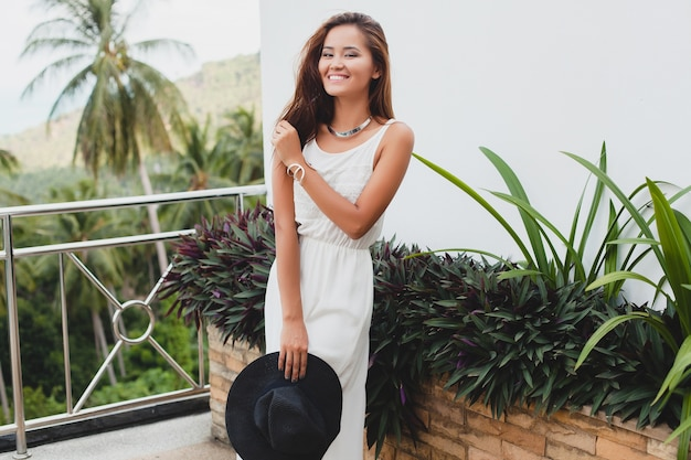 Young stylish asian woman in white boho dress, vintage style, natural, smiling, happy, tropical vacation, hotel, honey moon