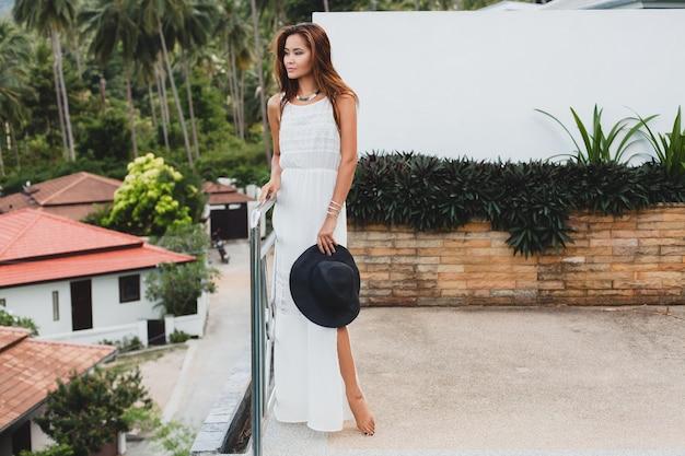 Giovane donna asiatica alla moda in abito bianco boho, stile vintage, naturale, sorridente, felice, vacanza tropicale, hotel, sfondo di palme