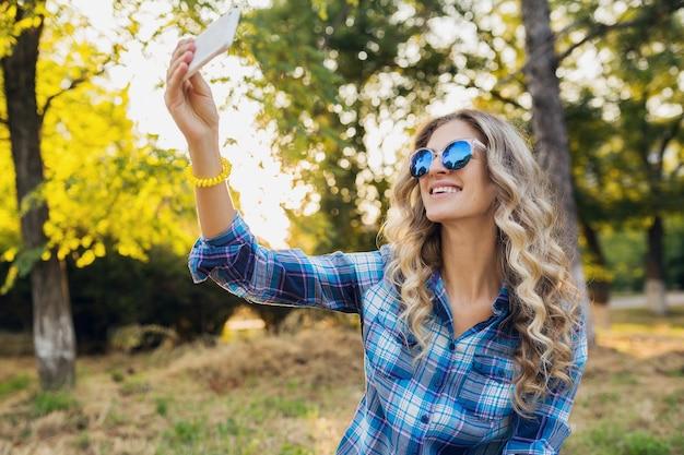 Молодая стильная привлекательная улыбающаяся белокурая женщина, сидящая в парке, делая селфи фото по телефону
