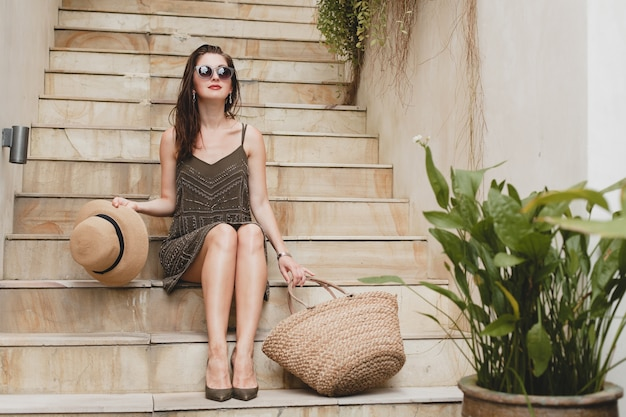 Young stylish attractive woman in elegant dress sitting on stairs, straw hat and bag, summer style, fashion trend, vacation, smiling, stylish accessories, sunglasses, posing on tropical villa on bali