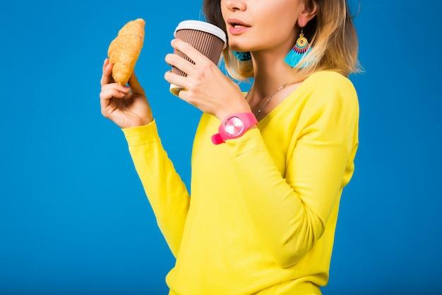 青に黄色のブラウスの若いスタイリッシュな魅力的な女性