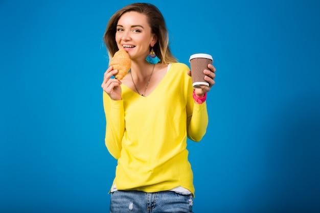 Giovane donna attraente alla moda in camicetta gialla sull'azzurro